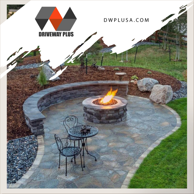Firepit in pavers on a stone patio with a retaining wall.